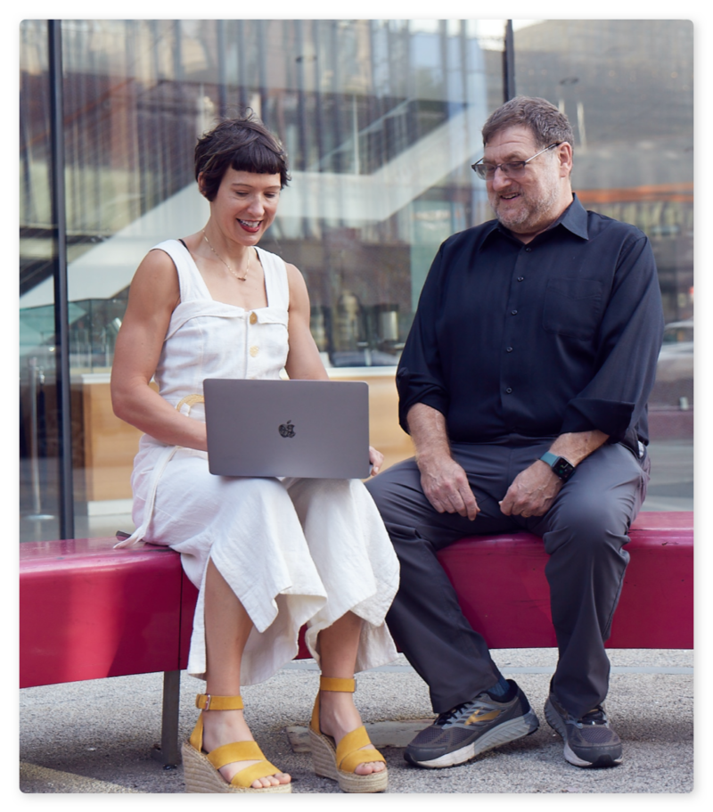 Alia and Mark, smiling and looking at a laptop